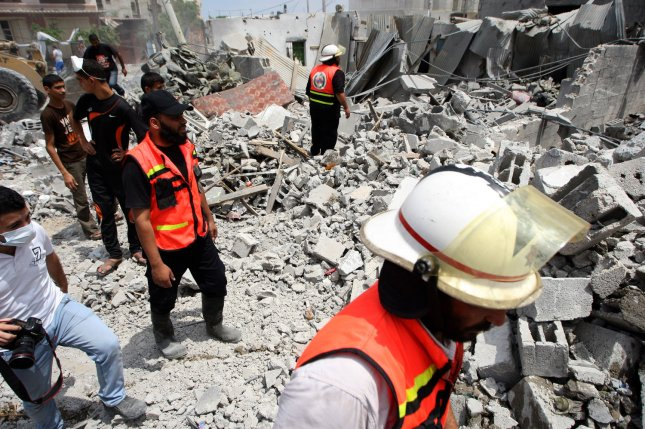 Palestinian rescue workers stand on the rubble of buildings as they search for victims of the Israeli military attack close to the Rafah refugee camp in southern Gaza Strip, on August 4, 2014. UPI/Ismael Mohamad