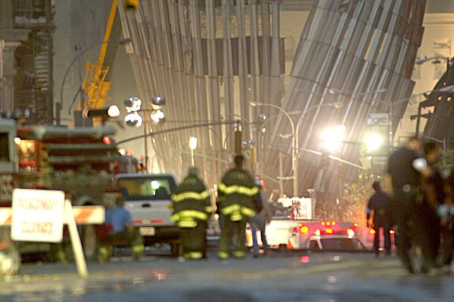 New York City firefighters observe the remnants of the World Trade Center's North Tower an hour before the sun began to rise over New York City the day after two hijacked commercial airplanes were flown into the Twin Towers, destroying the World Trade Center. File Photo by Steven E. Frischling/UPI