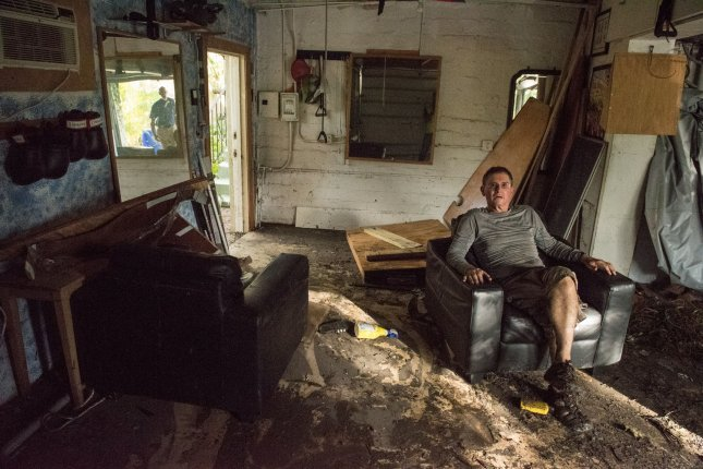 Paul Naron takes a quick break from cleaning up his flooded house after Hurricane Irma struck in Coconut Grove, Florida on September 11. Photo by Ken Cedeno/UPI