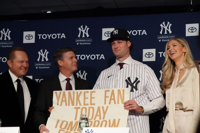 Scott Boras (L) and Hal Steinbrenner (L-C) look on as Gerrit Cole holds a sign from his youth with Amy Cole as the New York Yankees hold a press conference introducing their new pitcher Wednesday at Yankee Stadium in New York City. Photo by Bryan Smith/UPI