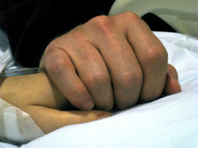 This Jan. 9, 2011, photo released by Congressworman Gabrielle Giffords' office shows the hand of her husband, Mark Kelly, over hers in a Tucson hospital.UPI/Rep. Gabrielle Giffords Office/Handout