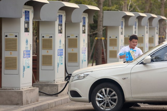 A man waits for his Chinese electronic vehicle to be powered-up at one of many charging stations in Beijing. File Photo by Stephen Shaver/UPI
