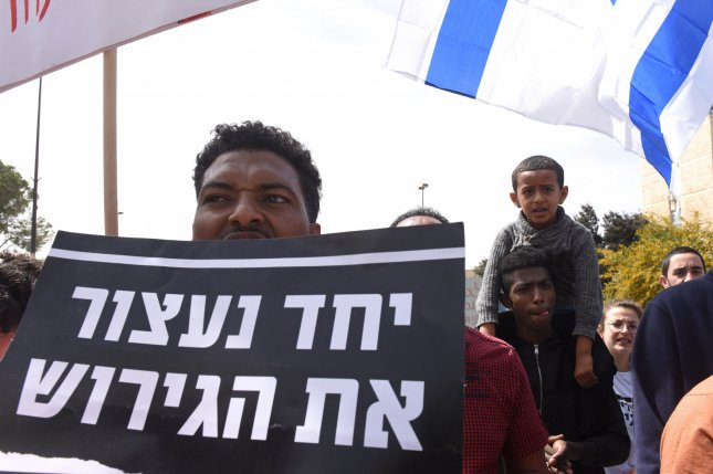 Israelis and African asylum seekers hold a sign reading, Together We Will Stop The Deportation, at a protest outside Israeli Prime Minister Benjamin Netanyahu's office in Jerusalem on Tuesday. Photo by Debbie Hill/UPI