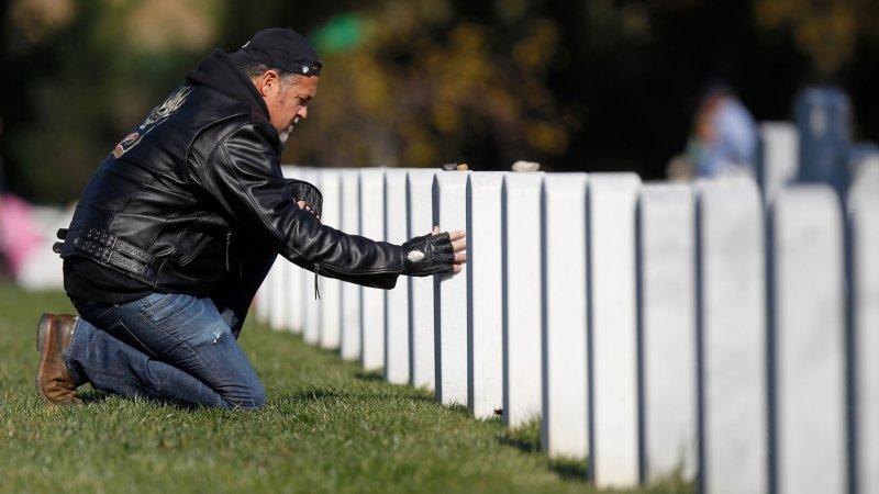 A man visits a grave site in section 60 during Veterans Day at Arlington National Cemetery in Arlington, VA, November 11, 2012. UPI/Molly Riley
