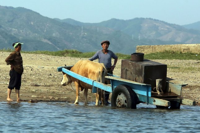 A North Korean waits for a small pontoon to cross a tributary on the banks of the Yalu River near Sinuiju, across the Yalu River from Dandong, China's largest border city with North Korea. North Korea faces food shortages owing to issues embedded in the country's agriculture, including insufficient arable land. Photo by Stephen Shaver/UPI