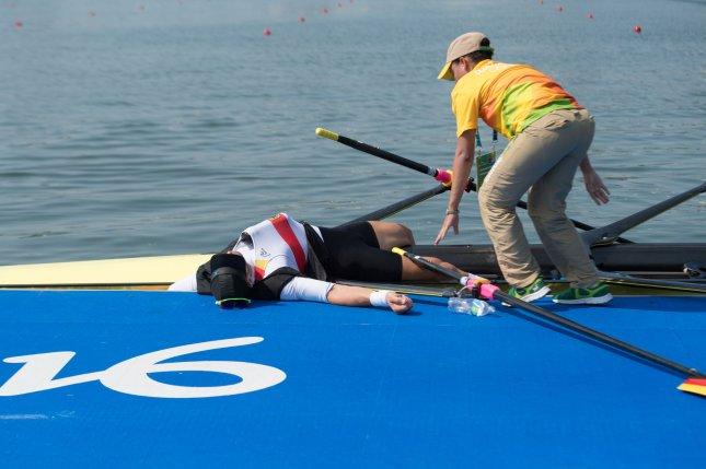 Marcel Hacker of Germany collapses on the dock after coming in forth in the men's double skulls rowing during the 2016 Summer Olympics in Rio de Janeiro, Brazil, August 9, 2016. Hacker recovered and suffered only from exhaustion. Photo by Richard Ellis/UPI..