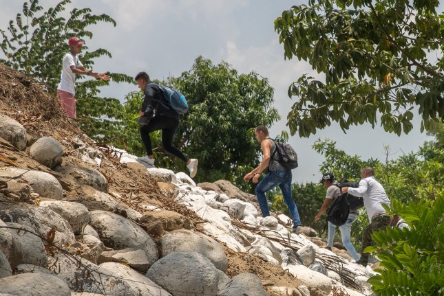 Migrants follow a smuggler after riding an inflatable raft on the Suchiate River from Tecun Uman, Guatemala to Ciudad Hidalgo, Mexico on May 9. Photo by Ariana Drehsler/UPI