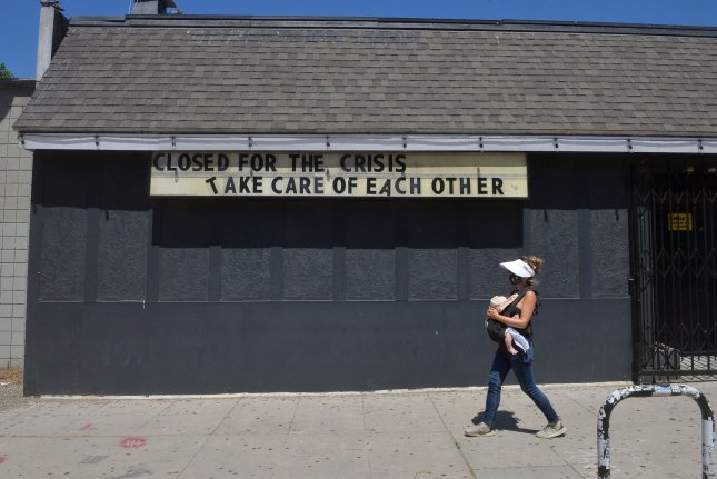 A woman walks past a closed tavern Monday in the Silver Lake area of Los Angeles.  Photo by Jim Ruymen/UPI