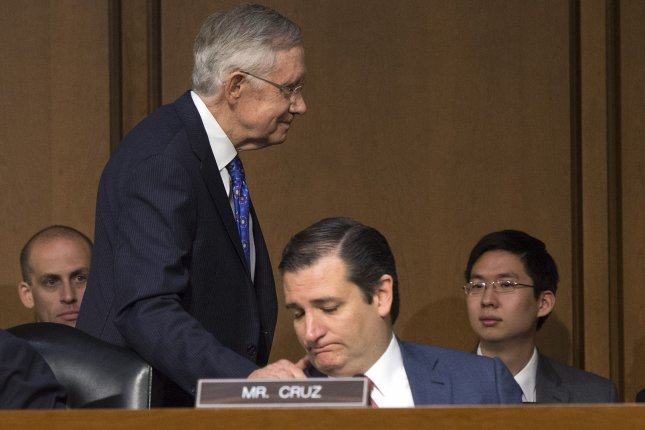 Senate Majority Leader Harry Reid (D-NV) places his hand on Sen. Ted Cruz's (R-TX) shoulder after testifying during a Senate Judiciary Committee hearing on a constitutional amendment on campaign finance, on Capitol Hill in Washington, D.C. UPI/Kevin Dietsch