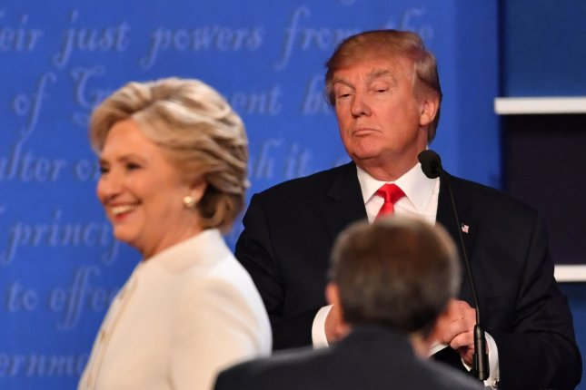 Democratic presidential candidate Hillary Clinton smiles as she walks between moderator Chris Wallace and Republican presidential candidate Donald Trump following their debate at the University of Nevada, Las Vegas on October 19. On Tuesday, a Critical Issues Poll by the University of Maryland showed that the majority of respondents said they believe Clinton would do the most to advance women's interests as president -- while Trump would do the most to advance U.S. economic interests. File Photo by Kevin Dietsch/UPI