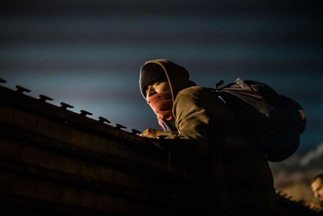 A young man traveling with the migrant caravan looks over the fence to see if he can see the U.S. Border Patrol as he and others attempt to cross the border fence in Tijuana, Mexico on December 26, 2018. The U.S. government is in a partial shutdown due to a funding argument about the border. Photo by Ariana Drehsler/UPI