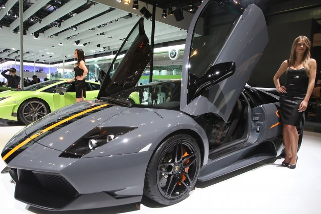 Models pose next to Lamborghini sports cars at Beijing's international Auto China car show. (File/UPI/Stephen Shaver)