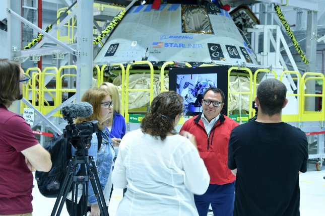 Boeing senior operations lead Ramon Sanchez (right of center) discusses Wednesday the condition of the Starliner capsule, which is being refurbished at Kennedy Space Center in Florida. Photo by Joe Marino/UPI
