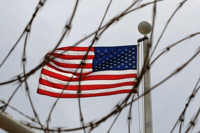 An American Flag is seen through razor wire at Camp 6 in Camp Delta at Naval Station Guantanamo Bay in Cuba. Photo by Roger L. Wollenberg/UPI