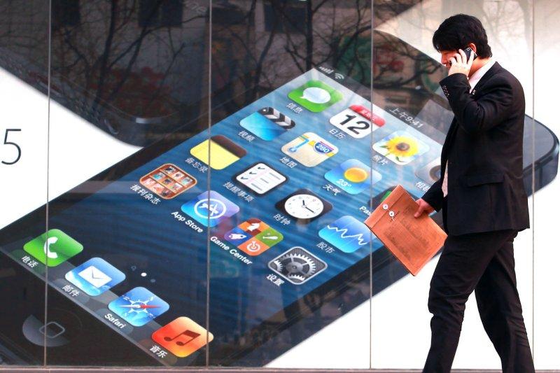 A man walks past an authorized Apple retailer. (File/UPI/Stephen Shaver)