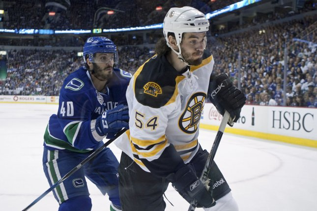Boston Bruins Adam McQuaid looks for the puck ahead of Vancouver Canucks Maxim Lapierre during the first period of the first game of the Stanley Cup Final at Rogers Arena in Vancouver British Columbia on June 01, 2011. UPI/Heinz Ruckemann