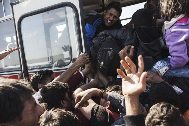 Refugees and migrants try to jam on buses near the border crossing with Serbia In Roszke, Hungary on September 8, 2015 as they seek asylum in Germany. That country expects about 300,000 new migrants this year on top of the 1 million it has already allowed in to Germany. File Photo by Achilleas Zavallis/UPI