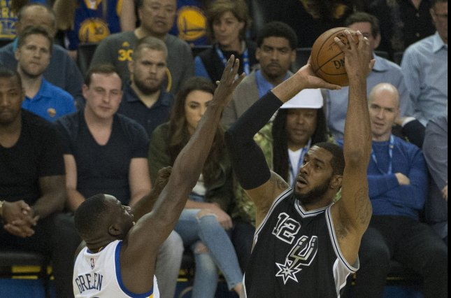 San Antonio Spurs Lamarcus Aldridge, at right, puts up a shot against Golden State Warriors Draymond Green on April 7, 2016, during a loss to the Warriors allowing them to clinch the top seed in last season's playoffs. File photo by Terry Schmitt/UPI