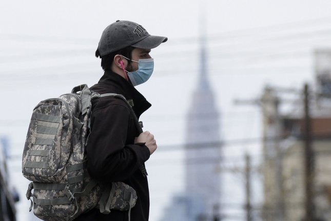 A pedestrian wearing a protective face mask crosses an intersection near Wyckoff Heights Medical Center in New York City on Tuesday. Photo by John Angelillo/UPI