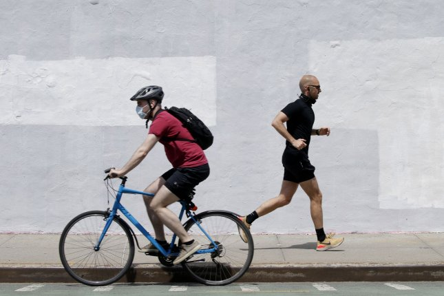A bicyclist rides while wearing a protective face mask to prevent the spread of coronavirus near Domino Park in New York City on May 17. Photo by John Angelillo/UPI