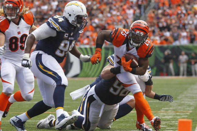 Cincinnati Bengals running back Giovani Bernard (25) fights to break free from Chargers defensive lineman Corey Liuget (94) and Sean Lissemore (98) during the second half of play on September 20, 2015 at Paul Brown Stadium in Cincinnati, Ohio. File photo by John Sommers II/UPI