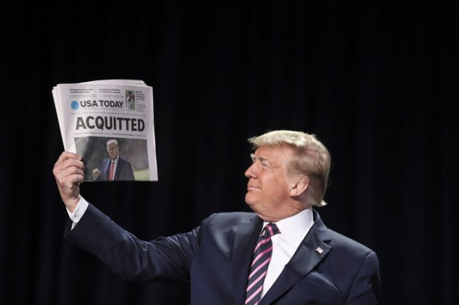 President Donald Trump holds a newspaper heralding his acquittal in the Senate as he arrives at the National Prayer Breakfast at the Washington Hilton on Thursday. Photo by Oliver Contreras/UPI