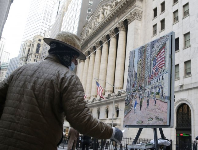 Artist Jim Chillington paints a picture of the New York Stock Exchange before the closing bell in New York City on Tuesday. The Dow Jones Industrial Average closed above the 30,000 mark for the first time in history. Photo by John Angelillo/UPI