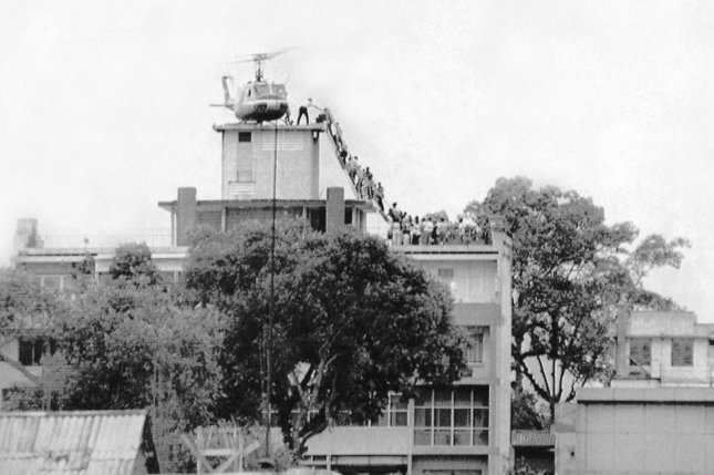 An Air America helicopter crew member helps evacuees up a ladder on the roof of 18 Gia Long Street on April 29, 1975 shortly before Saigon fell to advancing North Vietnamese troops. It's the iconic image of defeat. File Photo by Hugh Van Es/UPI