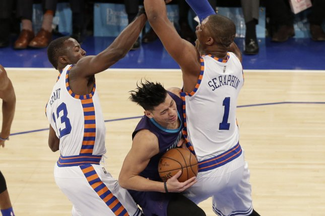 Former Charlotte Hornets G Jeremy Lin reacts when he makes contact with New York Knicks Kevin Seraphin and Jerian Grant in the second half at Madison Square Garden in New York City on November 17, 2015. The Knicks defeated the Hornets 102-94. Photo by John Angelillo/UPI