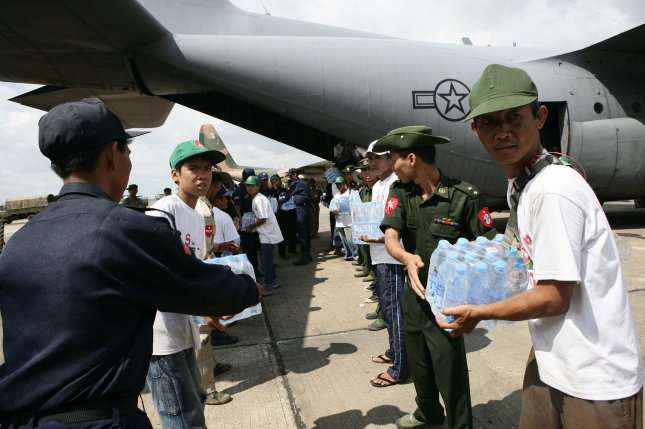Myanma service members form a line to unload water supplies from a U.S. Air Force C-130 Hercules aircraft at Rangoon International Airport in Myanmar on May 12, 2008. The shipment of water, mosquito nets and blankets arrived on the first of three planned relief flights to provide aid to citizens devastated by Tropical Cyclone Nargis. File Photo by Andres Alcaraz/U.S. Marine Corps