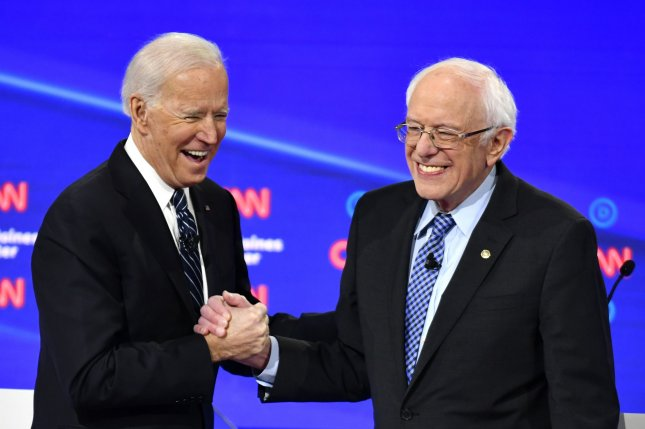 Former Vice President Joe Biden shakes hands with Vermont Sen. Bernie Sanders on stage at the primary debate in Des Moines, Iowa, on January 14. File Photo by CNN/UPI