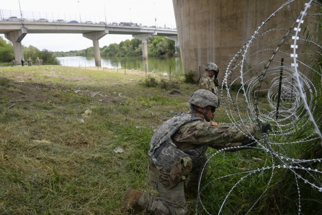 U.S. Army troops install concertina wire at the Hildago, Texas, port of entry on the U.S.-Mexico border. The deployment of 5,600 troops, scheduled to expire on Dec. 15, was extended on Tuesday to the end of January. File Photo by SrA Alexandra Minor/U.S. Air Force