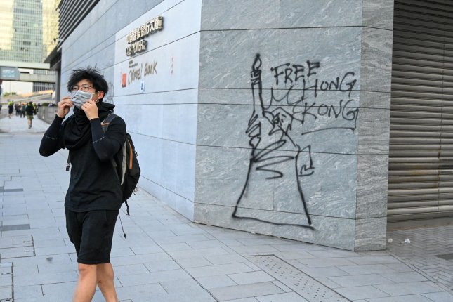 A protester walks near graffiti calling for a free Hong Kong in Hong Kong. Photo by Thomas Maresca/UPI