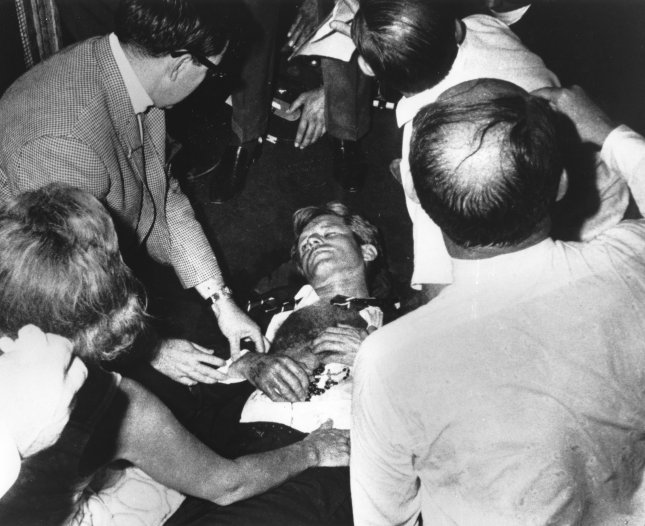 Clutching his rosary beads, Sen. Robert F. Kennedy lies injured on the floor of the Ambassador Hotel, after being shot by assailant Sirhan Bashira Sirhan on June 5, 1968, following his victory speech in the California primary election. Kennedy's wife Ethel is at lower left. UPI File photo