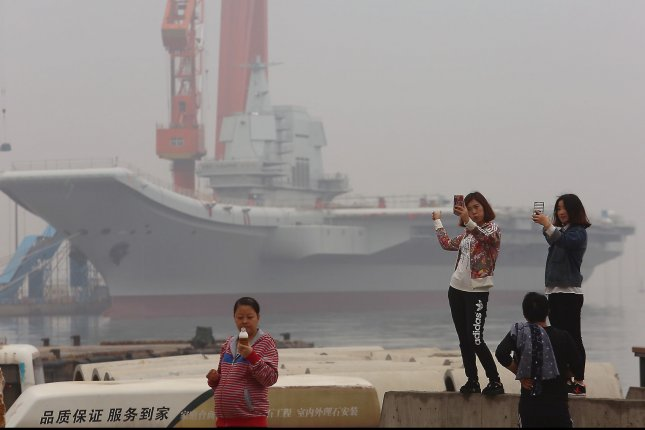 Chinese girls take selfies with China's second aircraft carrier, currently called the 001A, parked in a shipyard in the port city of Dalian in Liaoning Province, on May 4. Photo by Stephen Shaver/UPI