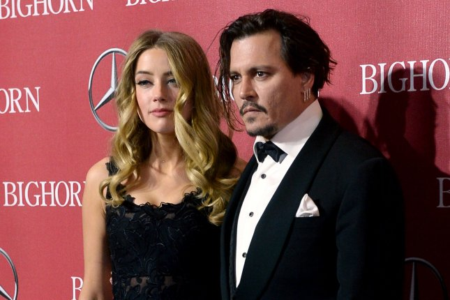 Amber Heard (L), pictured with Johnny Depp, accused the actor of physical abuse after filing for divorce in May 2015. File Photo by Jim Ruymen/UPI