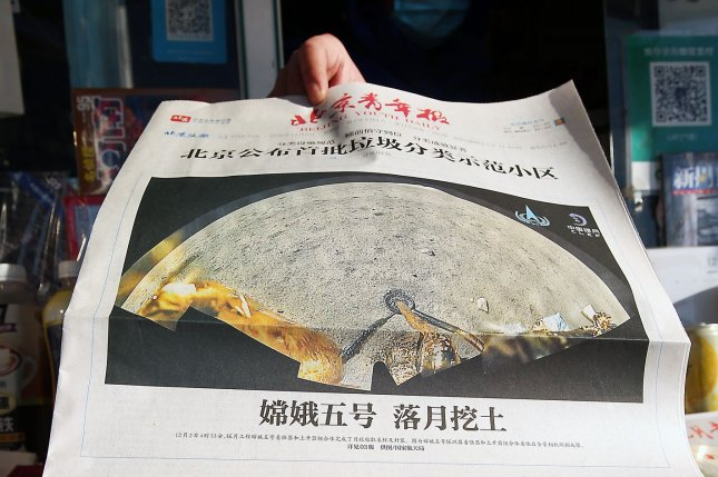 A news vendor in Beijing on Thursday displays a front page story of China's lunar probe successfully landing on the moon, not long before the probe finished taking samples of the moon's surface and sealed them within the spacecraft for their return to Earth. Photo by Stephen Shaver/UPI