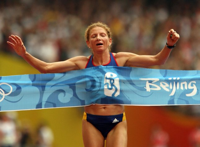 Romania's Constantina Tomescu Dita sprints through the tape at the finish line a good 100 meters in front of the pack to win gold in the Olympic Women's Marathon event in Beijing August 17, 2008. Dita won in 2h26:44. Kenya's Wincatherine Nyambura Ndereba edged out China's Chunxiu Zhou by a second to win silver with a time of 2h27:06. (UPI Photo/Stephen Shaver)