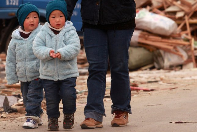 Chinese twins are taken for a cold, early-morning walk in Beijing on October 17, 2013. UPI/Stephen Shaver
