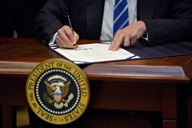 President Donald Trump signs H.J. Res. 57 during a ceremony in the Roosevelt Room of the White House on March 27. Pool photo by Andrew Harrer/UPI