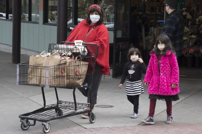 A family leaves a grocery store with supplies in San Francisco in this March photo. On Friday the U.S. Department Agriculture announced it is recalling763,000 poundsof pepperoni Hot Pockets that may be contaminated with glass or hard plastic. Photo by Terry Schmitt/UPI