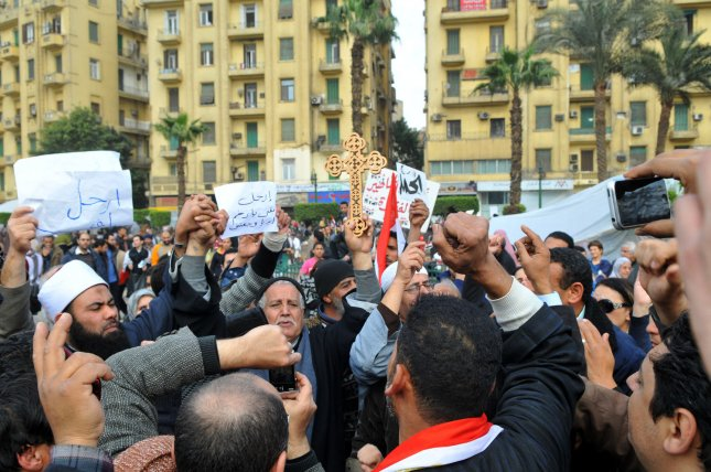 Egyptian Coptic Christians and Muslims raise a Cross and the Muslim holy book, the Koran, on the 13th day of protests in Tahrir Square in central Cairo calling for the end to President Hosni Mubarak's regime on February 6, 2011. UPI