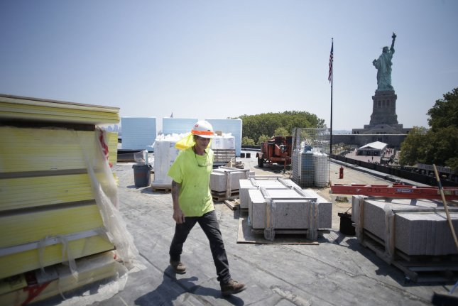 Construction workers walk near the new Statue of Liberty Museum in New York City on July 2. Photo by John Angelillo/UPI