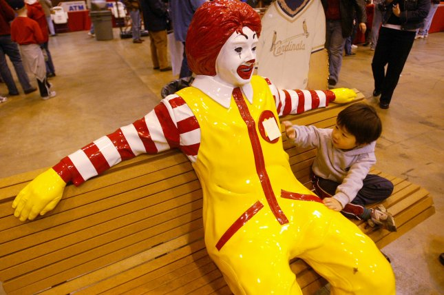 A child tries to get the attention of a Ronald McDonald statue. File photo by Bill Greenblatt/UPI