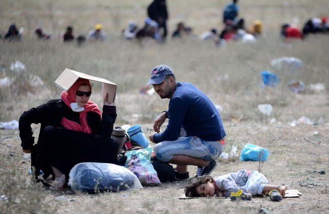 A Syrian family waits on the border near the town of Gevgelija, Macedonia, last fall, among hundreds of refugees seeking permission to get into the country. Refugees clashed with police Monday as they attempted to tear down a razor wire fence separating a Greek refugee camp from Macedonia. File Photo by Borce Popovski/UPI