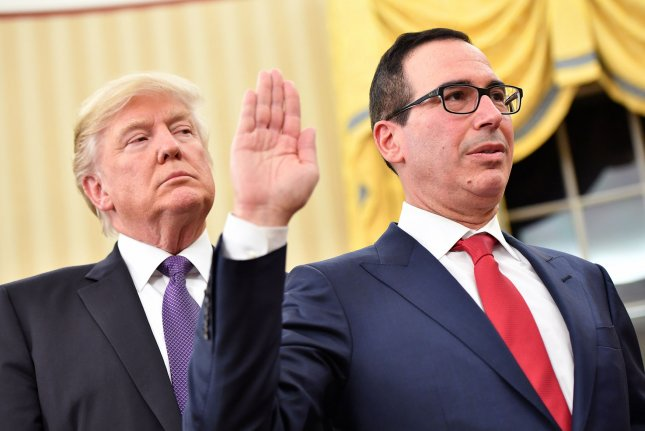 President Donald Trump looks over the shoulder of Treasury Secretary Steven Munchin as he is sworn in during a ceremony at the White House in Washington, D.C. on Monday. Mnuchin was confirmed by the Senate 53-47 earlier today. Photo by Kevin Dietsch/UPI