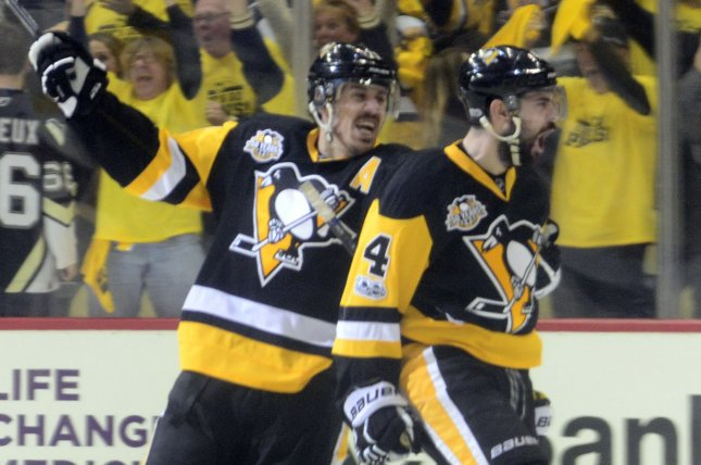 Pittsburgh Penguins center Evgeni Malkin (71) celebrates with Pittsburgh Penguins defenseman Justin Schultz (4) during the third period. File photo by Archie Carpenter/UPI