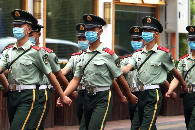 Chinese soldiers wear protective face masks as the march back to their barracks after changing guard in Beijing's embassy district on Thursday. Despite the easing of restrictions and the lowered threat of COVID-19 in China's capital, the government still requires people to wear face masks when in public areas. The nation is 21st in the world in deaths with 4,634 and its mortality rate is 5.5 percent, about 1 percentage point above the world rate. Photo by Stephen Shaver/UPI