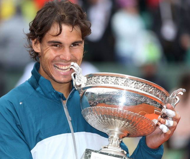 Rafael Nadal, striking his traditional bite-the-trophy pose after he won the 2013 French Open, could retake the No. 1 spot in the ATP world rankings with a strong showing -- and some help regarding Novak Djokovic -- in the U.S. Open. UPI/David Silpa