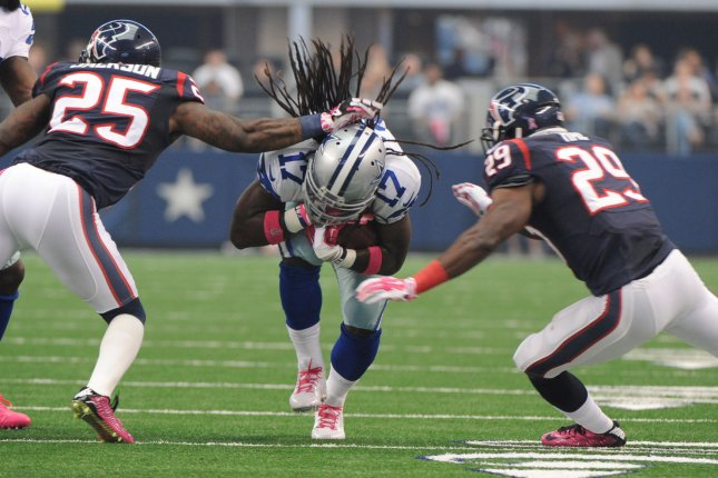 Dallas Cowboys wide receiver Dwayne Harris lunges forward as Houston Texans cornerback Kareem Jackson (25) and safety Andre Hal (29) close in during the first half on October 5, 2014 at AT&T Stadium in Arlington, Texas. File photo by Ian Halperin/UPI
